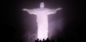 MEMBERS OF MEDIA SEEN IN FRONT OF CHRIST THE REDEEMER STATUE IN NIGHTTIME VIEW